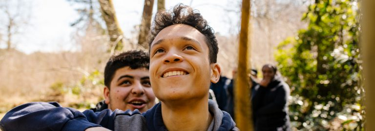Young person smiling, walking in woods