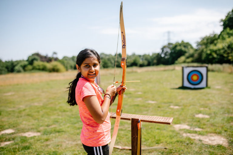 young girl shoots archery bow at Woodrow High House Outdoor Learning Centre