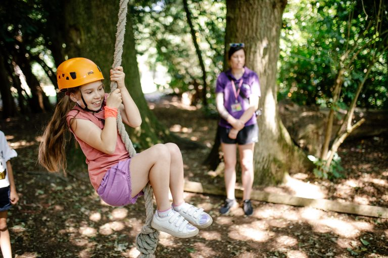 Girl swings on rope swing activity at Woodrow High House