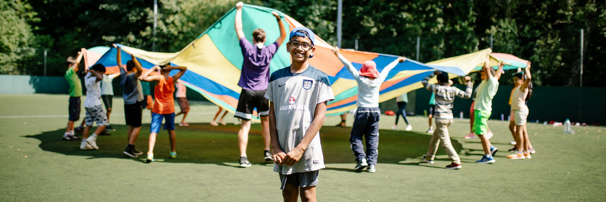 Boy stands in front of group waving colour parachute whilst on a school trip at Woodrow High House